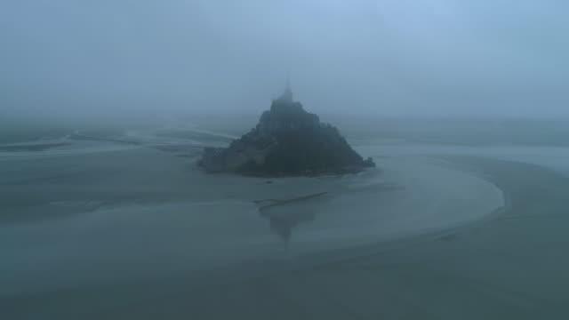 vidéos et rushes de aerial: mont saint-michel emerges from sandy beach immersed in dense fog - normandy, france - moyen âge