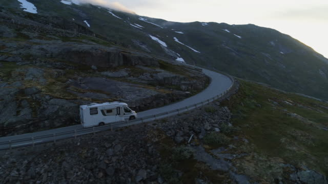 aerial: motor home drives on winding road over mountain with snow against sky during winter - dalsnibba mountain plateau, norway - camper van stock videos & royalty-free footage