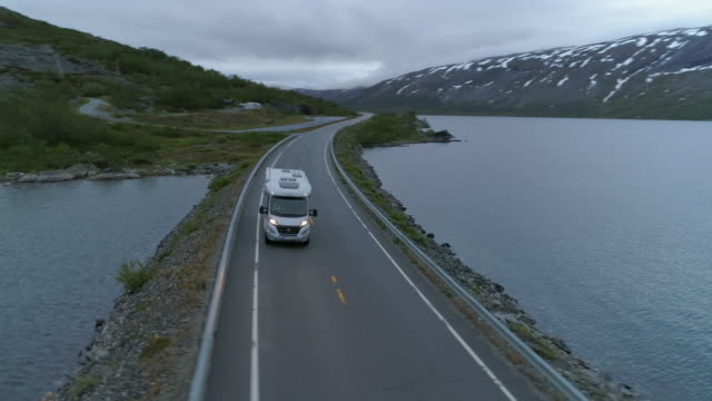 aerial: motor home travels through highway amidst lake by mountains against sky during winter - geiranger fjord, norway - land vehicle stock videos & royalty-free footage