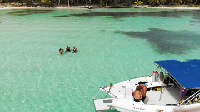 stockvideo's en b-roll-footage met aerial: motorboats, sailboats and yachts floating in front of tropical beach - buitenbad