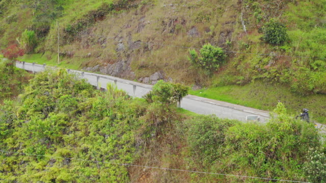 aerial: motorcycle riding on road leading to rock of guatape in guatape, colombia - オートバイ点の映像素材/bロール