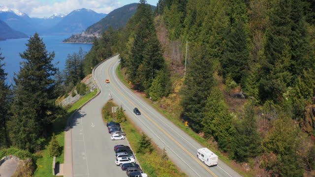 aerial: motorhome along with vehicles moving on highway by trees and fjord during sunny day - lions bay, british columbia - british columbia stock videos & royalty-free footage