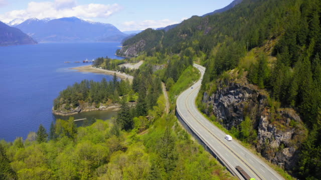 aerial: motorhome on highway over mountain by fjord, vehicles on road by trees during sunny day - lions bay, british columbia - british columbia stock videos & royalty-free footage