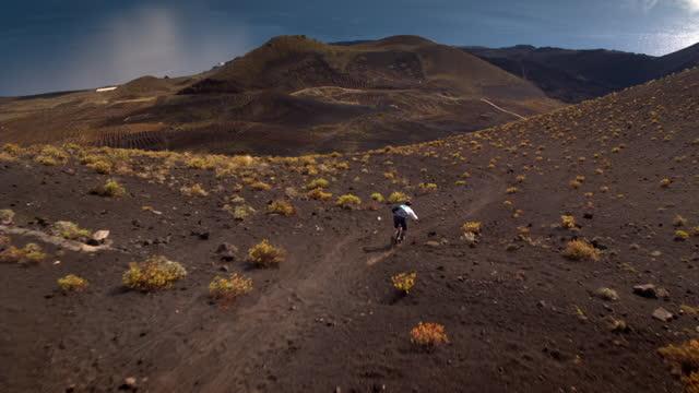 aerial mountain biker descends rocky mountain - アドレナリン点の映像素材/bロール