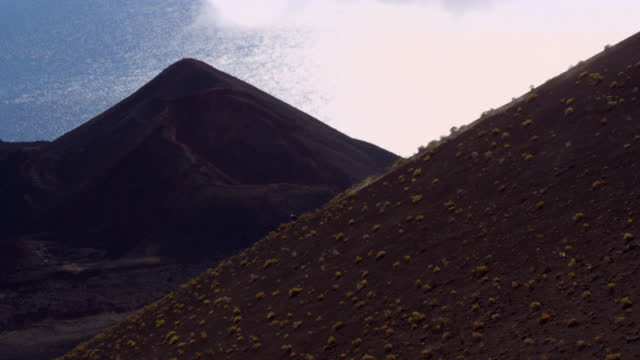 aerial mountain biker descends steep landscape - アドレナリン点の映像素材/bロール