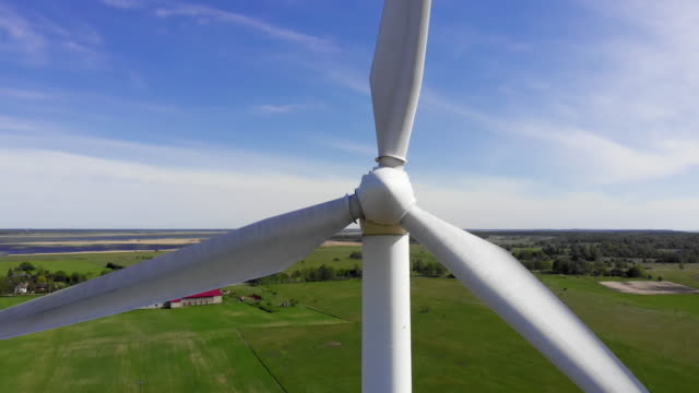 aerial move up: close view of windmill rotating blades on blue sky - blade stock videos & royalty-free footage