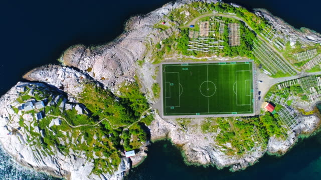 4k aerial movie flyover henningsvaer village public football field in lofoten island, norway - drone stock videos & royalty-free footage