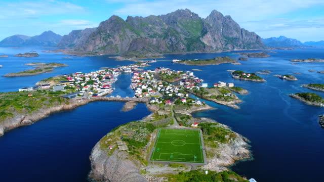 stockvideo's en b-roll-footage met 4k luchtfoto film viaduct henningsvaer dorp openbare voetbal veld in lofoten eiland, noorwegen - voetbal bal