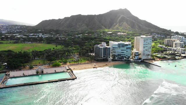 aerial moving away from a group of people on a tropical resort beach with palm trees, gentle waves, and steep rugged mountains in the background - oahu, hawaii - hotel stock videos & royalty-free footage
