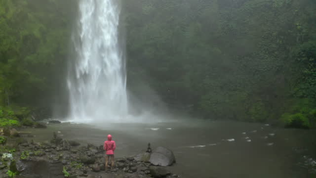 vidéos et rushes de aerial moving backward away from soaring waterfall surrounded by lush vine-covered cliffs with a woman hiker, cool rising mist, and a rocky river - nusa penida & lombok, bali - endroit isolé