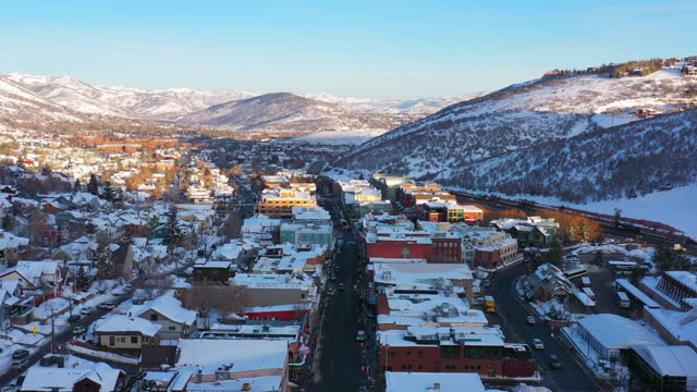 aerial moving backwards over a snow covered mountain ski town with quiet streets and bright morning sunlight - park city, utah - park city stock videos & royalty-free footage