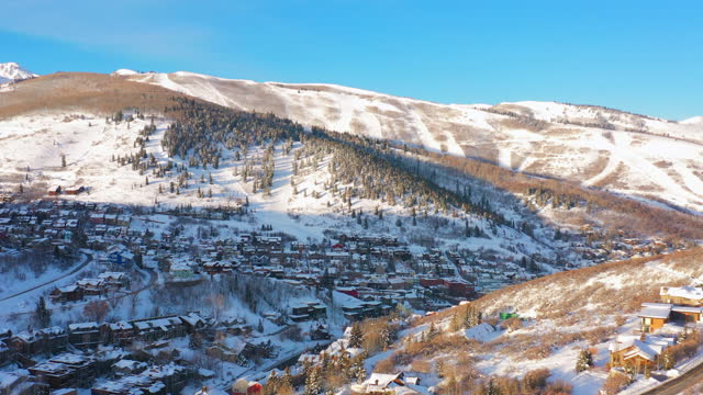 aerial moving backwards over a snow covered mountain town with quiet streets and bright morning sunlight - park city, utah - park city stock videos & royalty-free footage