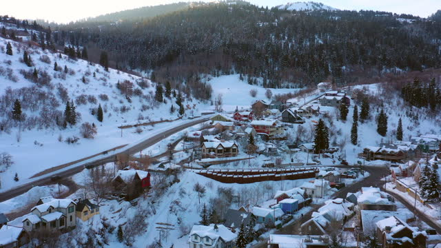 aerial moving backwards over a snowy mountain ski town with quiet streets and bright morning sunlight - park city, utah - park city stock videos & royalty-free footage