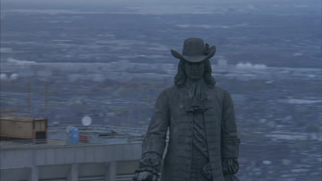 aerial moving pov circling the william penn statue on top of the philadelphia city hall. see blur of houses and buildings in background. - william penn stock videos and b-roll footage