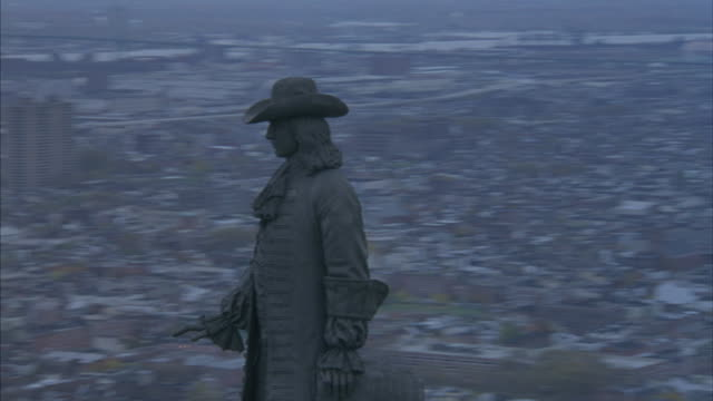 aerial moving pov circling the william penn statue on top of the philadelphia city hall. pov pulls back at end to show philadelphia skyline in background. see skyscrapers including one liberty place, two liberty place, and mellon bank center. - william penn stock videos and b-roll footage