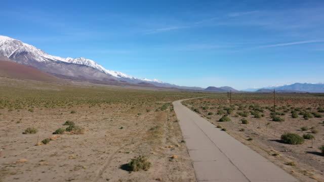 aerial: moving down narrow road near sierra nevada mountains - sierra nevada, california - narrow stock videos & royalty-free footage