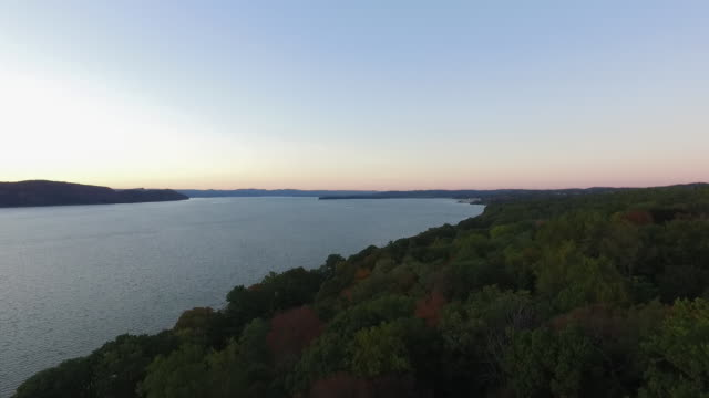 aerial pov moving down river over hudson river and trees at sunset - hudson river stock videos & royalty-free footage