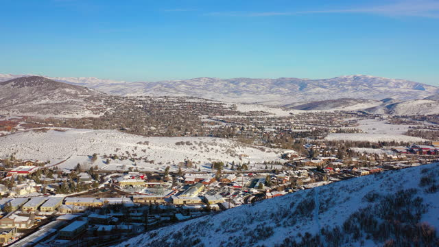 aerial moving forward high above residential neighborhood in a snowy mountain ski town with quiet streets and bright morning sunlight - park city, utah - park city stock videos & royalty-free footage