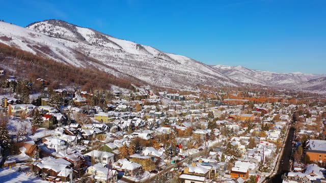 aerial moving forward over a residential neighborhood in a snowy mountain ski town with quiet streets and bright morning sunlight - park city, utah - park city stock videos & royalty-free footage