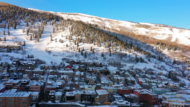aerial moving forward over a snow covered mountain ski town with quiet streets and bright morning sunlight - park city, utah - park city stock videos & royalty-free footage