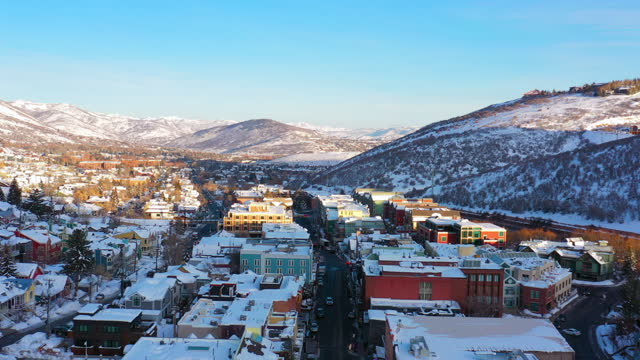 aerial moving forward over main street in a snowy mountain ski town with quiet streets and bright morning sunlight - park city, utah - park city stock videos & royalty-free footage