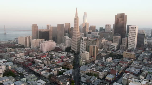 aerial moving forward towards amazing downtown skyline under a hazy sky with the oakland bay bridge in the background - san francisco, california - california street san francisco stock videos & royalty-free footage