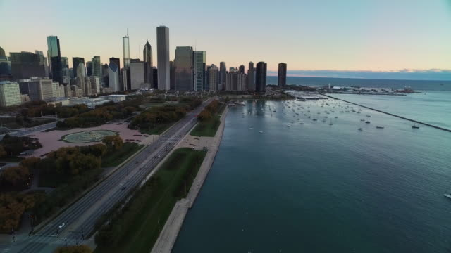 aerial moving north from buckingham fountain along lake shore drive into chicago skyline - buckingham fountain stock videos & royalty-free footage