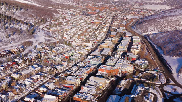 aerial moving over residential neighborhood in a snowy mountain ski town with bustling streets and bright morning sunlight - park city, utah - park city stock videos & royalty-free footage