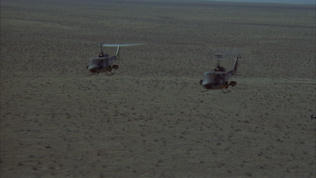 aerial moving pov flying among military helicopters over bare desert. pans between the different helicopters. see hueys and other smaller helicopter. see twelve helicopters total. - military helicopter stock videos and b-roll footage