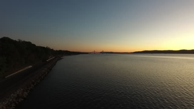 aerial pov moving south over hudson river at sunset - commuter train stock videos & royalty-free footage