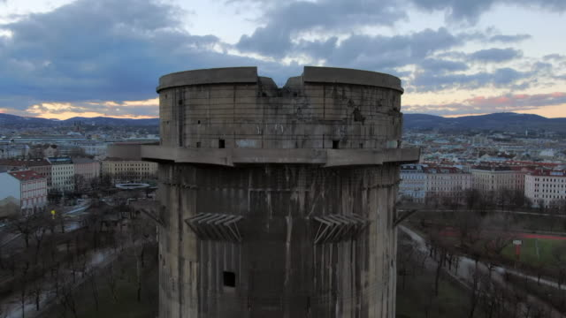 aerial: moving toward and up a flak tower in augarten park in vienna, austria - bunker struttura creata dall'uomo video stock e b–roll
