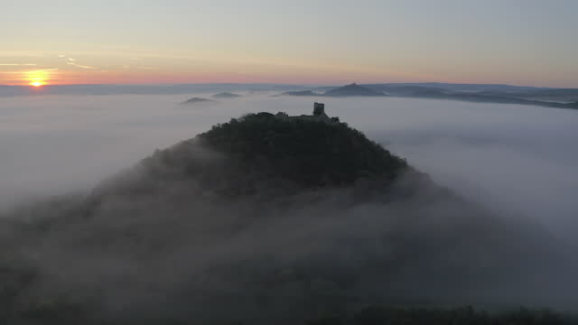 aerial moving towards burg gleichen, a historic castle ruins, high on a hill with lush green forests, foggy valleys and rolling countryside extending to the horizon - drei gleichen, germany - panning stock-videos und b-roll-filmmaterial