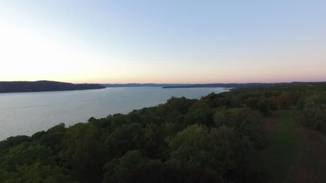 aerial pov moving up river over hudson river and trees at sunset - hudson river stock videos & royalty-free footage