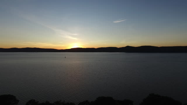 aerial pov moving up river over hudson river at sunset - hudson river stock videos & royalty-free footage
