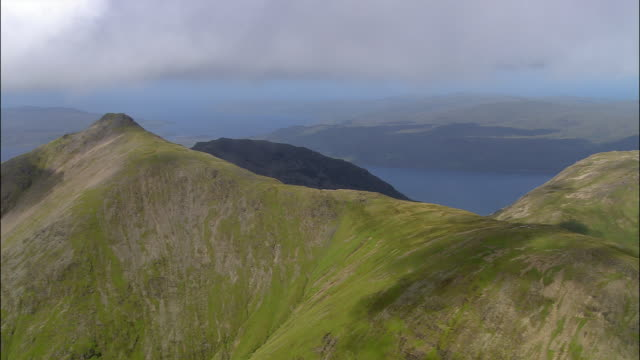 Aerial Munro of Ben More above shore of Loch na Keal / cloud-covered summit / Isle of Mull, Scotland