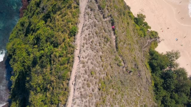 Aerial: Narrow Pathway on Ridge Between Rocky Shore and Sandy Beach