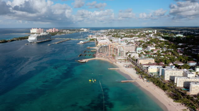 vídeos y material grabado en eventos de stock de aerial: nassau cityscape, beach, hotels, and huge cruise ship docked near shore - nassau