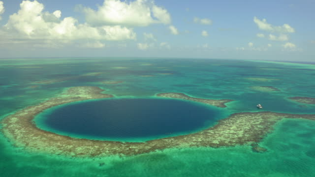 aerial: nautical vessel next to large marine sinkhole against sky, scenic view of seascape on sunny day - great blue hole, belize - nautical vessel点の映像素材/bロール