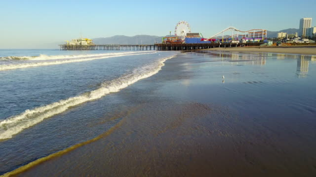 aerial near the sand of santa monica beach - santa monica pier stock videos & royalty-free footage