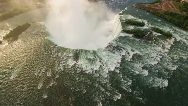 4k aerial niagara falls: horseshoe falls bathed in sunlight - niagara falls stock videos and b-roll footage