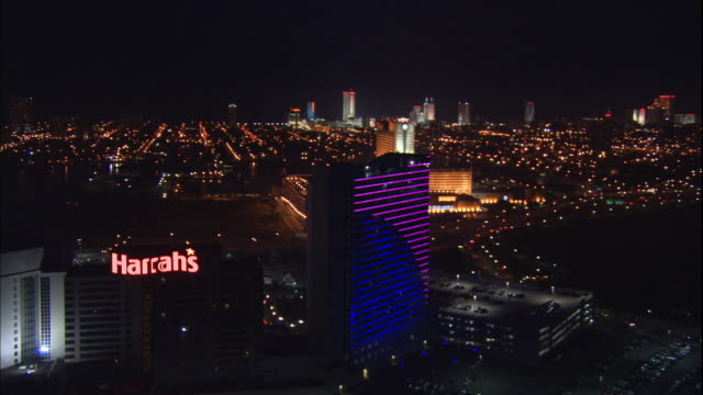 aerial; night; harrah's casino from out over absecon channel, fly over harrah's, fly over downtown towards casinos on northern end of shoreline. - atlantic city stock videos & royalty-free footage