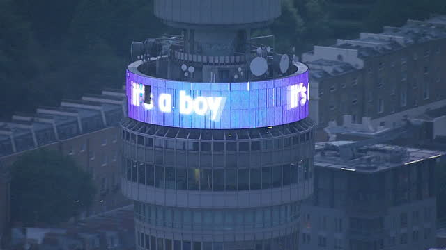 vídeos de stock e filmes b-roll de aerial night shots of bt tower with screens at top displaying scrolling message 'it's a boy' reaction as the duchess of cambridge has given birth to... - bt tower londres