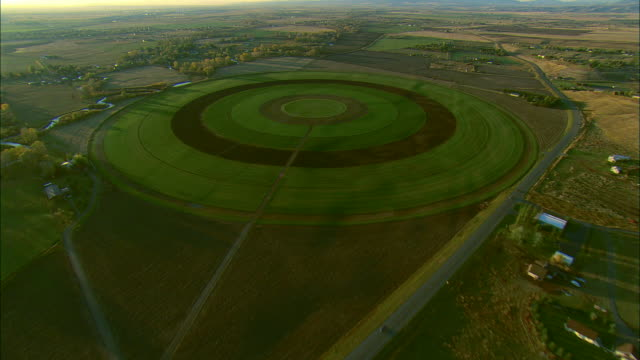 aerial oblique shot of large crop irrigation circle near bozeman, mt - 放射円点の映像素材/bロール