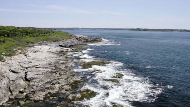 vidéos et rushes de aerial: ocean waves crash on rocks along a shoreline - newport, rhode island - rhode island