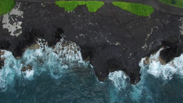 vídeos de stock, filmes e b-roll de aerial: ocean waves crashing on rocky, grassy shore - pedra material de construção