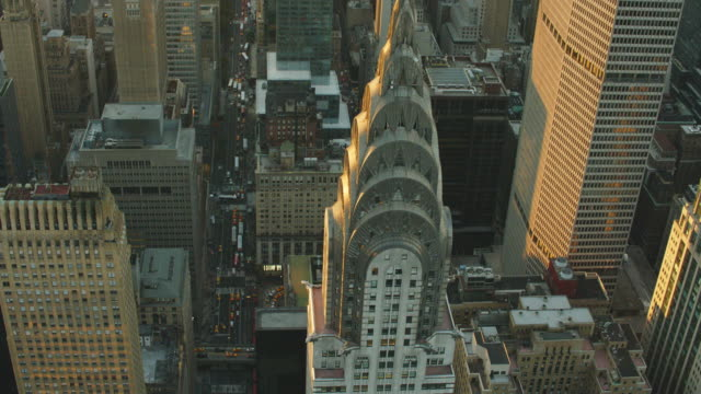 Aerial of 42nd street looking west and flying right over tip of Chrysler building
