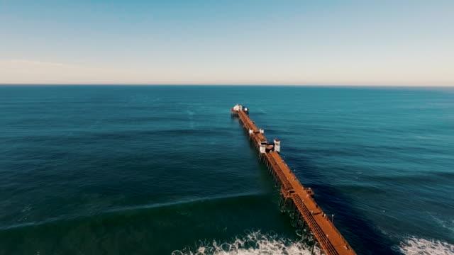 Luftaufnahme von einer wunderschönen Sonnenaufgang auf das glitzernde Meer, während die pier nie zu enden scheint in der blauen Abgrund zusteuert.