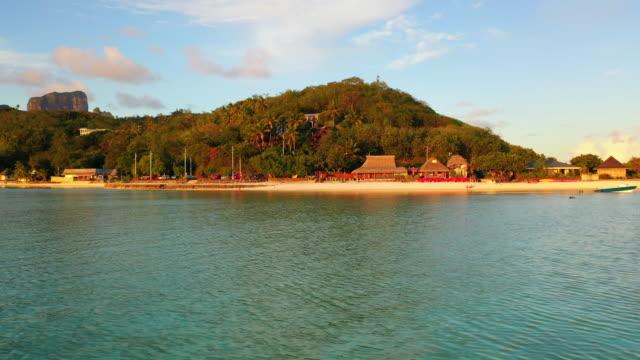 aerial of a beautiful tropical beach at dusk, drone flying backwards while ascending - bora bora, french polynesia - bak och fram bildbanksvideor och videomaterial från bakom kulisserna
