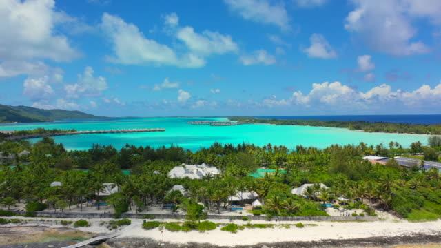 aerial of a beautiful tropical island in a bright blue lagoon, drone flying backwards while ascending - bora bora, french polynesia - bak och fram bildbanksvideor och videomaterial från bakom kulisserna