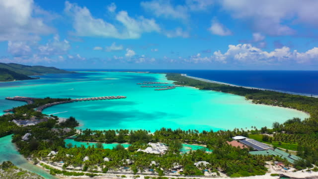 vidéos et rushes de aerial of a beautiful tropical island with helicopter landing pad in a bright blue lagoon, drone flying forward then tilting down - bora bora, french polynesia - bora bora